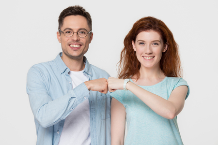 Happy smiling young woman and man friends couple give fist bump looking at camera as friendship partnership respect concept being team together isolated on white grey blank studio background portrait.