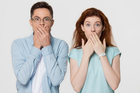Shocked scared amazed couple covering mouth with hands feel horrified stunned looking at camera, surprised mute man and woman astonished about unexpected news isolated on white grey studio background 스톡 콘텐츠