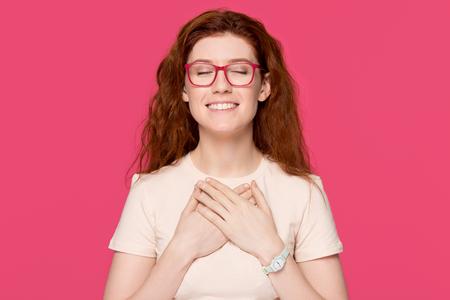 Fröhliche, dankbare, hoffnungsvolle rothaarige Frau, die Hand auf der Brust nah am Herzen hält, fühlt aufrichtige Wertschätzung, Liebe Dankbarkeit Ehrlichkeit, dankbare, erfreute, berührte rothaarige Dame einzeln auf rosa Studiohintergrund Standard-Bild