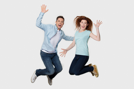 Happy cheerful young couple friends jumping together feeling free, excited energetic man and woman winners celebrate win flying looking at camera screaming with joy isolated on white grey studio background