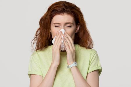 Allergische kranke rothaarige Frau, die laufende Nase im Gewebe bläst, bekam Allergiegrippe, kranke rothaarige Dame niesen mit Taschentuch einzeln auf weißem grauem leerem Studiohintergrund, Heuschnupfen-Rhinitis-Konzept Standard-Bild