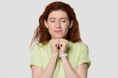 Hopeful redhead woman clenching fists making wish praying asking dreams come true, wishful red-haired woman in anticipation having desire believe in good luck isolated on grey white studio background Stock Photo