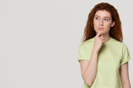 Thoughtful doubtful redhead young woman with unsure face holding hand on chin looking at copy space, red-haired teen girl feeling hesitant uncertain thinking isolated on white grey studio background