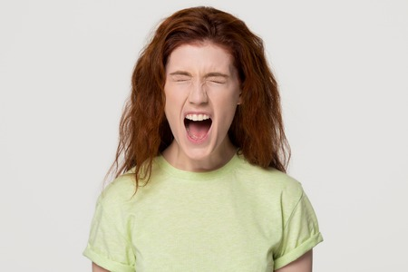 Angry stressed hysterical redhead woman with mad emotional face screaming yelling loud with rage, crazy furious red-haired girl shouting with anger isolated on white grey blank studio background