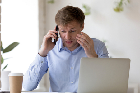 Upset millennial businessman sitting at desk in office or home talking on cellular with corporate client feels angry and irritated. Employee having serious problem at work got unpleasant news on phone Reklamní fotografie - 117286071