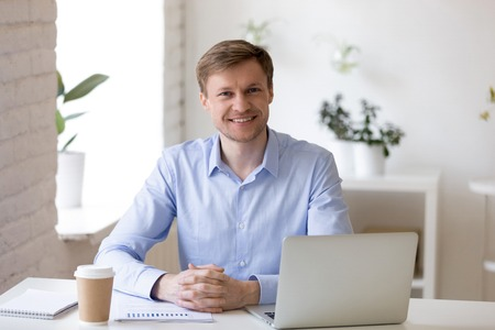 Attractive confident businessman or company employee wearing formal shirt sitting at desk opposite laptop in modern office smiling looking at camera. Leadership and successful business person concept Stockfoto