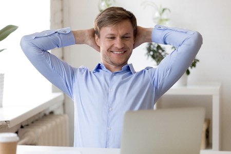 Businessman sitting at desk holding hands behind head looking at pc screen thinking relaxing after working day feels good. Successful positive company member has a good results completed work resting Stock Photo