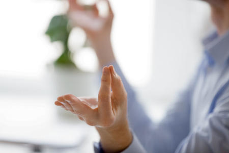 Close up male fingers folded in mudra gesture, office worker take break do yoga practice at workplace. Concept of stress relief healthy habit, mental healthcare and internal balance - key to wellbeing