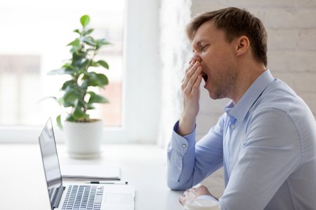 Millennial businessman yawning covering mouth with hand sitting at desk in the office while using computer. Exhausted bored man feels tired after long working day. Fatigue and lack of energy concept