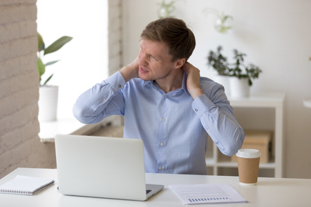 Millennial office worker sitting at desk near computer writhing in pain from neck ache touching sore neck feels unhealthy. Sedentary work, long time working without break and wrong posture concept