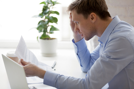 Frustrated man sitting at the desk in office reading notification from bank about unpaid debts. Stressed boss received letter with bad financial results, sales are down, problems in business concept Stock Photo