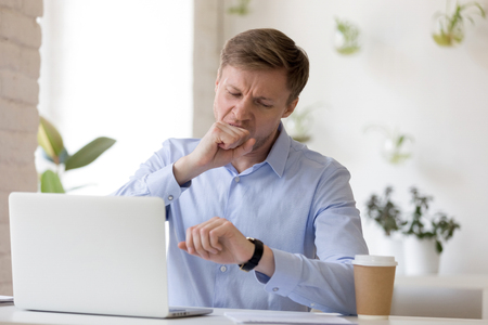 Exhausted or bored man sitting at desk in office looking at watch. Businessman yawning covering mouth with fist feels tired after busy hard working day. Chronic fatigue lack of energy or time concept