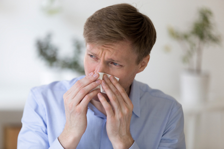 Head shot portrait of sick millennial man holding paper handkerchief and blowing nose feels unhealthy. Male suffers from cold, seasonal influenza or chronic allergy during working day at workplace