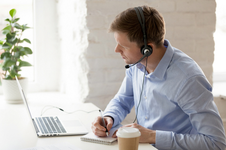 Businessman sitting at workplace improve knowledge use online lessons. Customer service operator wear headset listen client make notes solve problem distantly. Easy learning modern technology concept