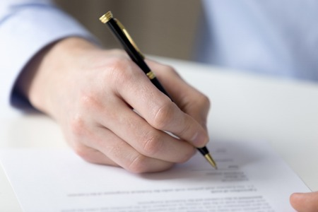 Customer sitting at table holds pen filling contract official document buy or sell property getting insurance or affirms employment agreement, close up paper and hand. Making successful deal concept