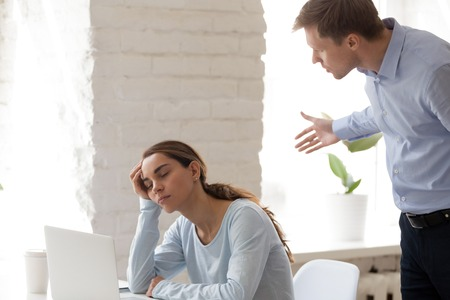 Angry company owner caught tired mixed race employee young woman when she fell asleep at workplace opposite laptop. Stressful work chronic fatigue lack of sleep or lazy and unmotivated worker concept
