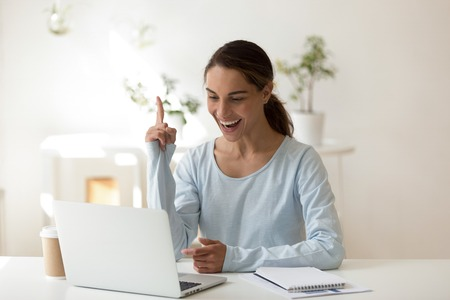 Young happy attractive woman sitting at desk working on computer raise index finger up she knows how to solve a problem, female having a brilliant idea. Creative approach in studies and work concept