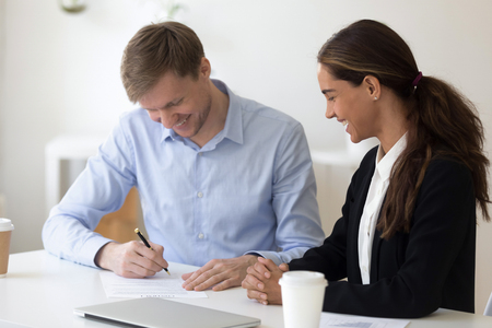Happy biracial businesswoman sitting at desk with business partner people gathered together in office for signing contract. Human resources or client getting receive services affirm official document