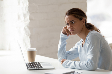 Mixed race student female sitting at table looking at computer screen feels bored and unmotivated to learning and studying preparing for exams. Inactive worker without the will and the energy to work
