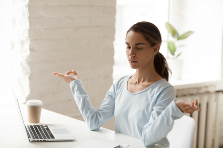 Mixed race young woman sitting at workplace reduces stress level and alleviates anxiety with meditation. Student distracted from learning and practising yoga exercises improve concentration and memory
