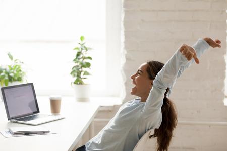 Fröhliche Mischlingsfrau, die am Arbeitsplatz auf dem Stuhl sitzt und sich streckt und die Hände hochhebt, fühlt sich glücklich, einen lang ersehnten Beitrag zu haben, der eine Online-Lotterie gewinnt oder einen Arbeitstag vor dem Urlaub erreicht Standard-Bild