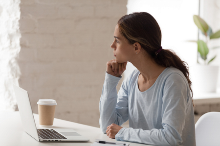 Mixed race concerned female sitting at workplace desk opposite computer holding head with hand thinking looking out the window having problems and doubts in making decision searching solution concept.