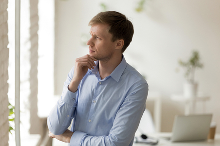 Serious concentrated millennial businessman standing alone in modern office room looking away touching stroking chin thinking about problem or making important decision planning new future projects.
