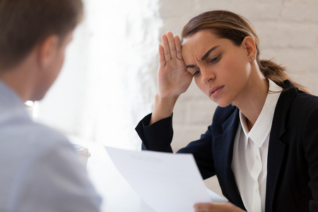 Confused hr manager holding in hand cv listening job candidature feels bewildered and perplexed, focus on female company representative. Bad negative first impression or unsuccessful interview concept