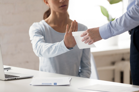 Woman sitting at workplace refuse money in the envelope offered by dishonest man, want to bribe employee for receiving something in exchange, cropped close up view. Anti bribery and corruption concept Foto de archivo