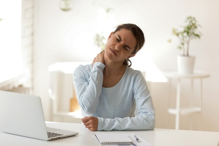Junge ungesunde gemischtrassige Frau, die am Arbeitsplatz sitzt und den Hals berührt, leidet unter Schmerzen. Schlechte Körperhaltung und sitzende Tätigkeiten, eingeklemmte Nerven, längerer Einsatz moderner Technik inkl. Computerkonzept Standard-Bild