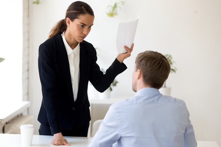 Angry millennial businesswoman standing opposite unqualified employee holding paper criticizing financial report telling about mistakes in document accusing company member feels irritated and outraged Stock Photo