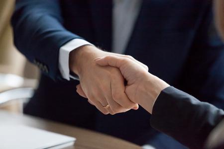 Geschäftsmann und Geschäftsfrau in Anzügen, die den Respekt des Partners zeigen, die Gleichstellung der Geschlechter, weibliche männliche Hände schütteln als Konzept für die vertrauensvolle Zusammenarbeit, Dankbarkeit, gute Beziehungen, Nahaufnahme Standard-Bild