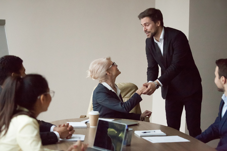Satisfied grateful partner employee holding shaking hand of executive thanking for help or opportunity, expressing respect and gratitude at team meeting, making feedback compliments flattering boss