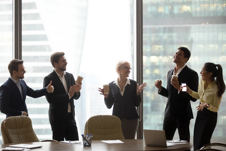 Happy friendly executive employees team dancing to mobile app music having fun together in office, diverse workers company staff group enjoy funny victory dance concept celebrating business success Stock Photo