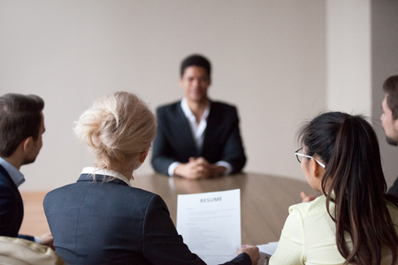 Rear view of hr managers group listen to african male applicant at job interview, recruiters employers talk to seeker making hiring decision meeting vacancy candidate, staffing recruitment concept Фото со стока - 117289215