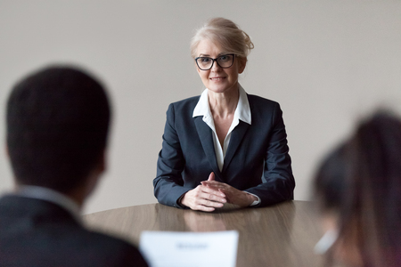 Smiling middle aged senior female job applicant listening to hr questions making first impression at interview, recruiters interviewing older mature candidate, recruitment, age and employment concept Stok Fotoğraf