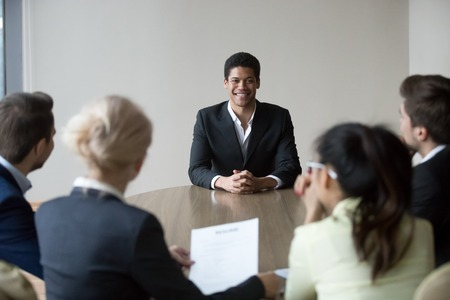 Smiling african black male applicant convincing hr managers employer to hire making first impression on recruiters feeling confident happy prepared to get job as good candidate for recruiting team.