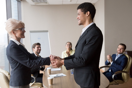African executive manager holding hand of successful caucasian worker express respect gratitude for good work dedication promote mature employee motivate shake hands, rewarding recognition concept Stock Photo