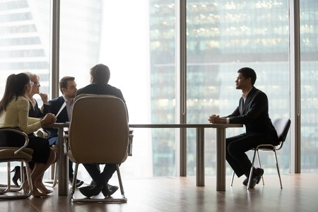 Hr team interviewing african male candidate sitting at big table in modern office, diverse recruiters talking to candidate making hiring decision for vacancy during job interview recruitment concept