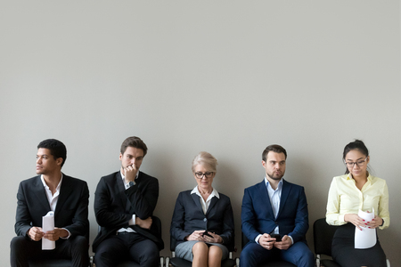 Multi ethnic applicants sitting in row queue line preparing for interview, diverse male female vacancy candidates waiting for their turn on chairs, human resources employment and job search concept
