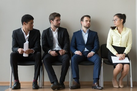 Diverse male applicants looking at female rival among men waiting for at job interview, professional career inequality, employment sexism prejudice, unfair gender discrimination at work concept Foto de archivo