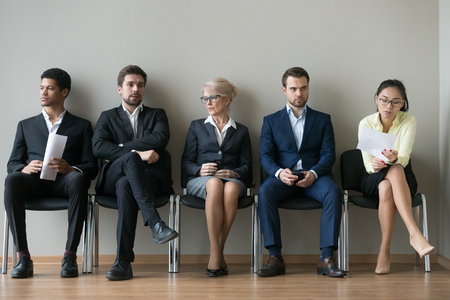 Diverse business people applicants sit in row line queue waiting for their turn, african, asian and caucasian unemployed seekers group preparing for job interview, human resources employment concept