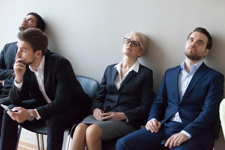 多様な応募者は、就職面接のコンセプトを待って退屈なキューラインの椅子に座って退屈し、疲れ果てた多民族の求職者は遅れや長い待ち時間に疲れました