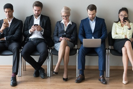 Diverse businesspeople applicants or customers sitting in row using devices phones and laptop, multi ethnic men women waiting for job interview in queue, human resources, people and gadgets concept