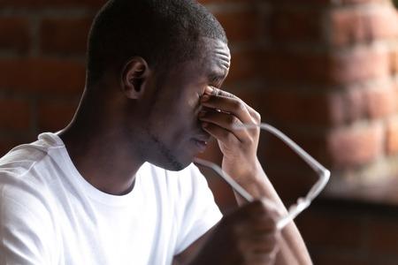 Gros plan sur un homme africain noir qui enlève des lunettes se sent malsain et souffre de fatigue oculaire après avoir longtemps travaillé sur ordinateur. Mauvaise vision et technologies modernes affectant négativement le concept de santé humaine