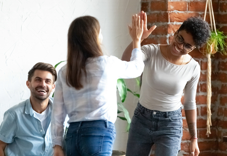 Caucasian mixed race young pretty women standing greeting giving high five glad to see each other. Best friends multi-ethnic girls and guys gathered together in cafeteria feels happy and satisfied