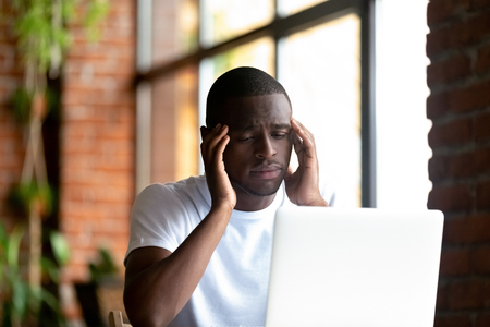 Boring black american millennial man sitting indoors looking at pc screen feels unwell. Students not interested in studying or employee disinterest in work. African man feeling lack of energy concept