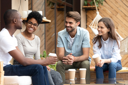 Four laughing diverse people positive multi-ethnic friends sitting in cozy cafe summer terrace drink coffee telling funny stories from life feels happy and satisfied enjoy time together on weekend. Stock fotó