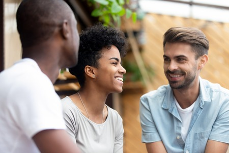 Three millennial multi-ethnic friends spending weekend together sitting in cafe or restaurant cozy summer terrace talking enjoying free time with each other, focus on laughing attractive african girl Stock Photo