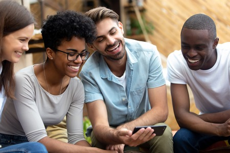 Cheerful young pretty diverse people sitting in outdoors cafe using internet wifi watching video or photo online. Smiling guy spending time with best friends showing them new interesting application Imagens - 117289572